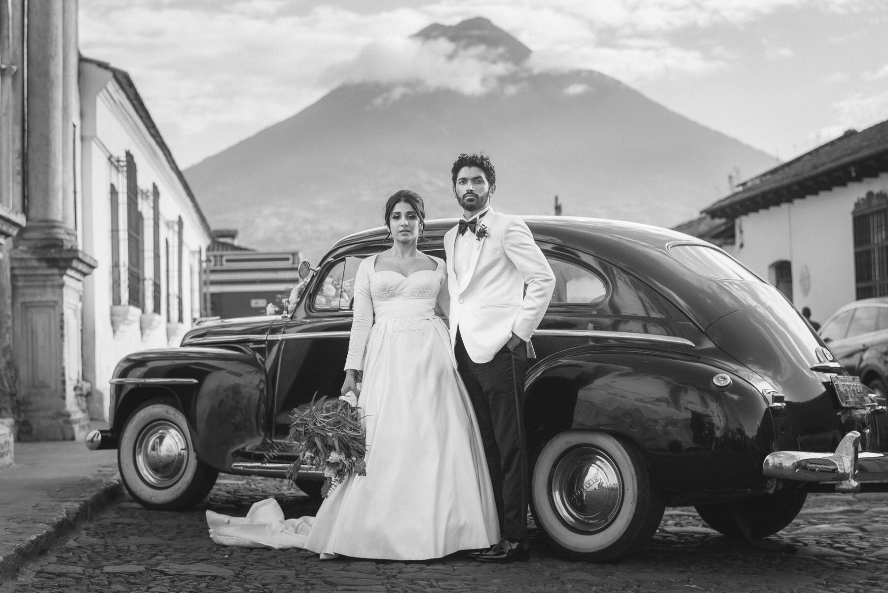 Indian couple posing in front of a classic car and a volcano in Antigua Guatemala