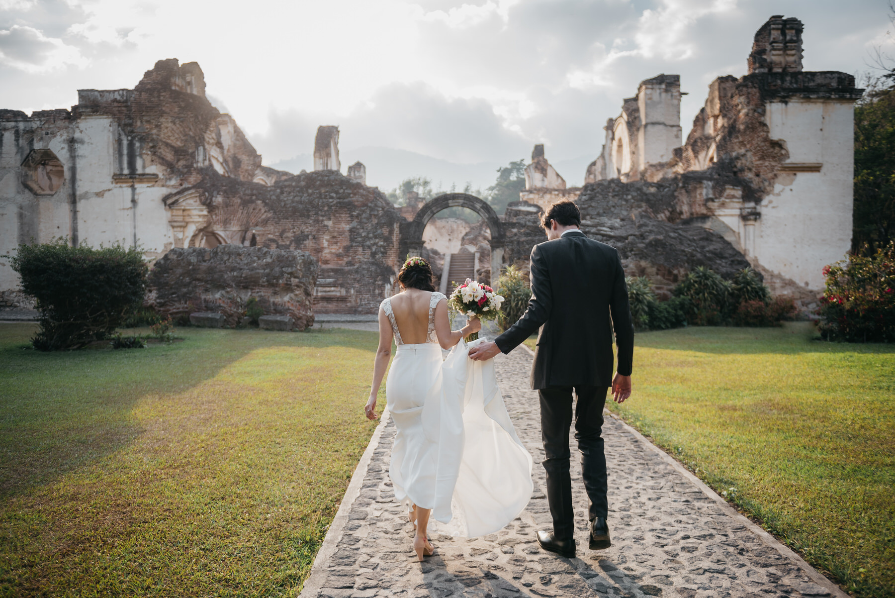 Bride and groom walk towards ruins of La Recoleccion in Antigua Guatemala